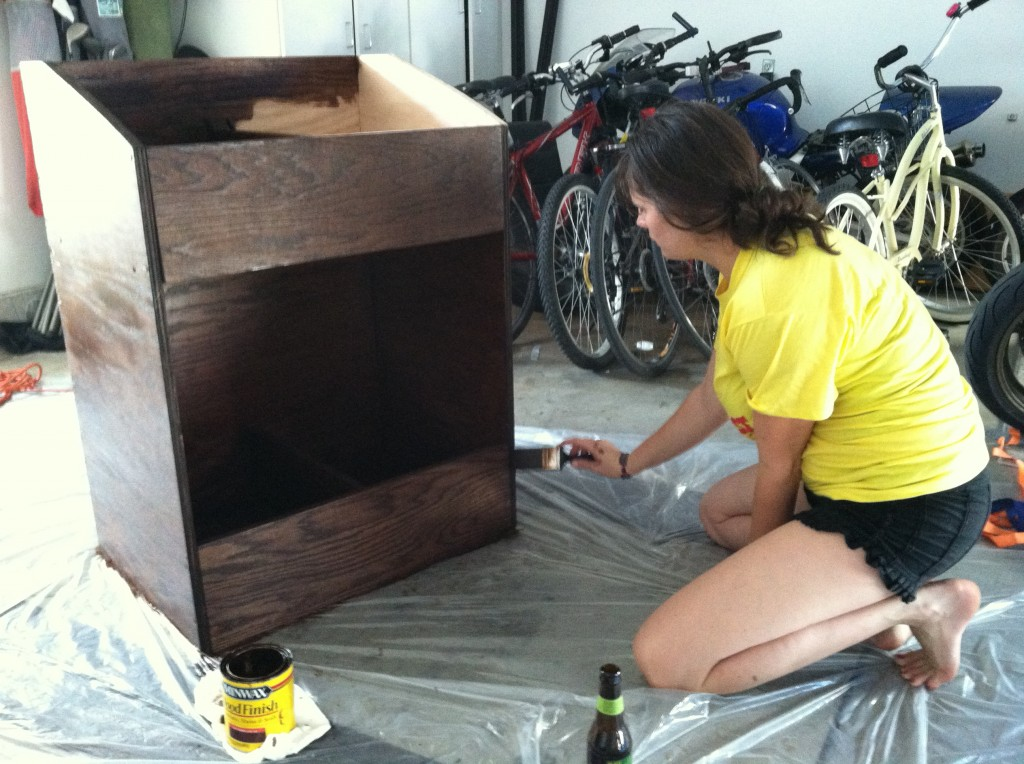Lauren applying a layer of polyurethane finish to the vinyl record shelf