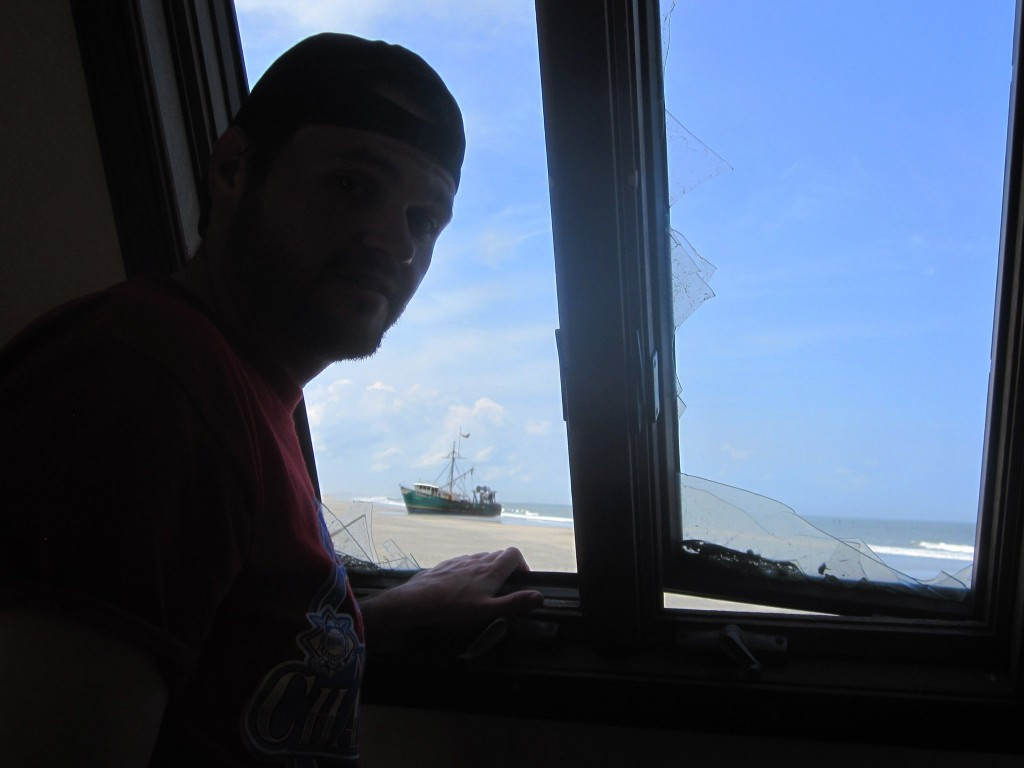 Looking out the broken window at an abandoned fishing boat